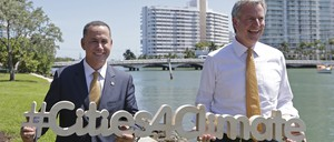 """Miami Beach Mayor Philip Levine, left, and New York City Mayor Bill de Blasio hold a sign reading """"Cities4Climate"""" in front of a waterway and apartments"""