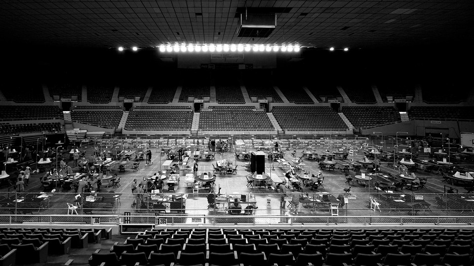 Maricopa County ballots cast in the 2020 general election are examined and recounted in a black-and-white photo of a sports arena.