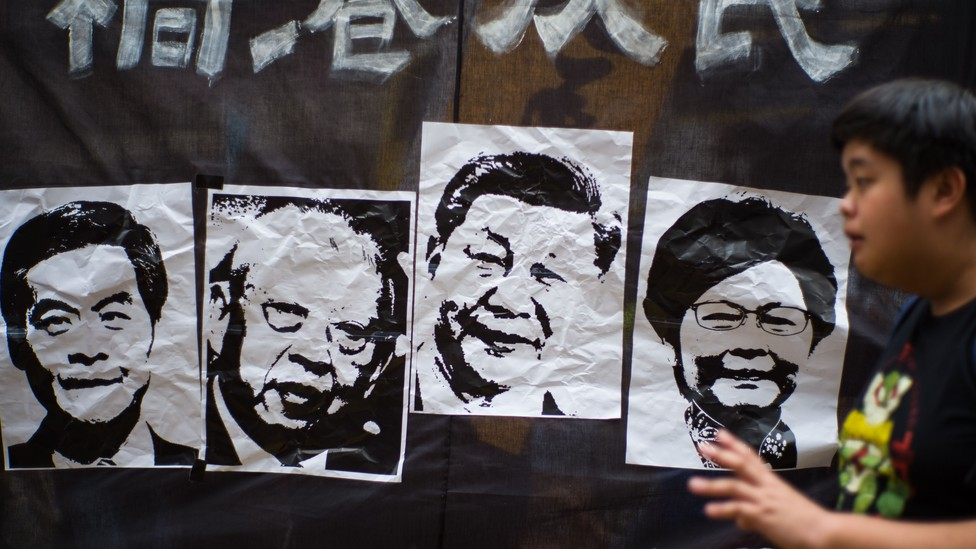 A man walks past a banner with pictures depicting the former Hong Kong chief executives Leung Chun-ying and Tung Chee-Hwa, as well as Chinese President Xi Jinping and Hong Kong Chief Executive Carrie Lam, during an annual National Day prodemocracy rally.