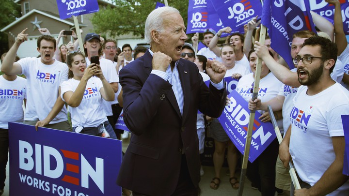 Joe Biden pumps his fists amid a group of young-adult supporters.