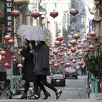 Two women cross in front of red lanterns hanging on Grant Avenue in Chinatown in San Francisco.