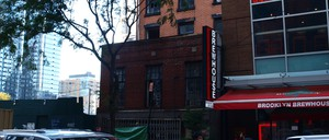 """An old house beside a modern building with a sign reading """"Brooklyn Cocktail Lounge"""""""