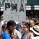 """A participant in the Paris gay pride parade holds up a placard which reads """"PMA (Fertility treatment) for all."""""""