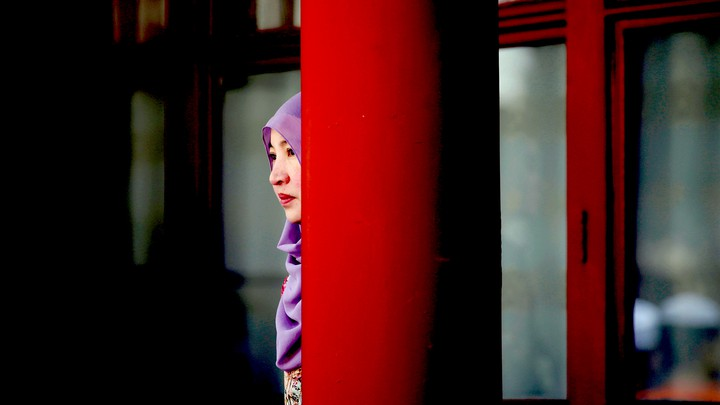 A woman stands behind a pillar during the Eid al-Adha festival at a Chinese mosque.