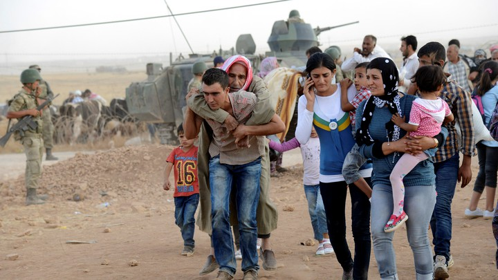 Syrian Kurds cross the border into Turkey, fleeing ISIS, in 2014.
