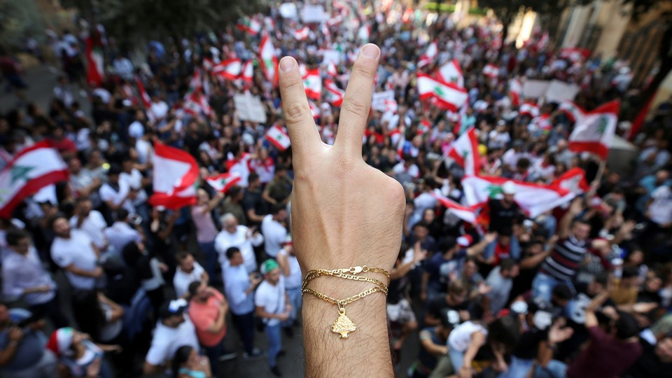A close up photo of a demonstrator flashing a V sign. In the background, protesters gather waving Lebanon flags.