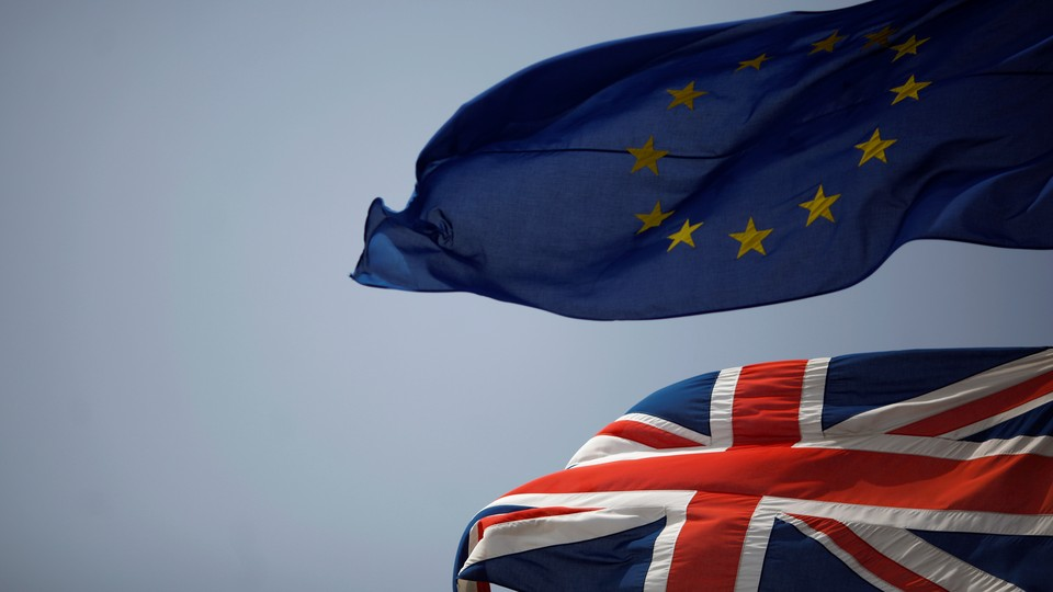 The Union Jack (bottom) and the European Union flag (top) are seen flying.