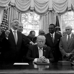President Trump, Vice President Mike Pence, and faith leaders say a prayer in the Oval Office in September 2017.Several people have their hands on Trump's shoulders. Most of the people have their eyes closed.