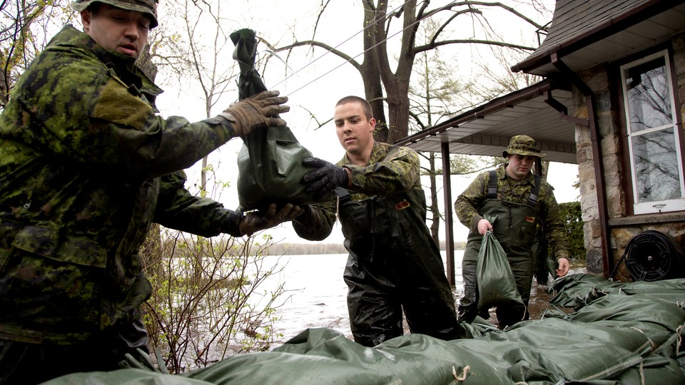 Canadian soldiers place sandbags outside a home in a flooded residential neighbourhood.