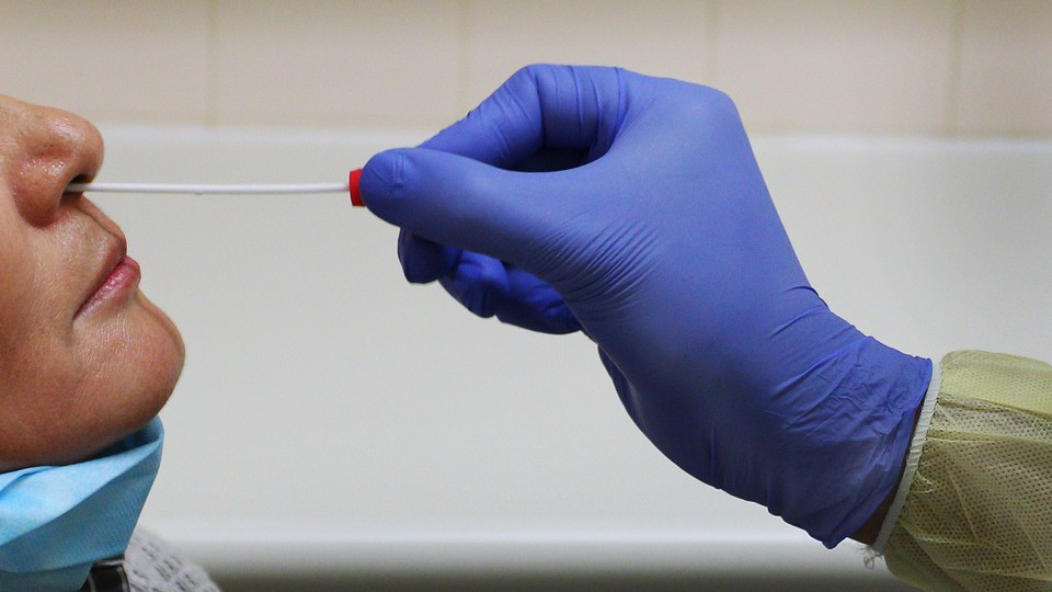A nurse inserts a swab into a person's nose to test them for a virus.