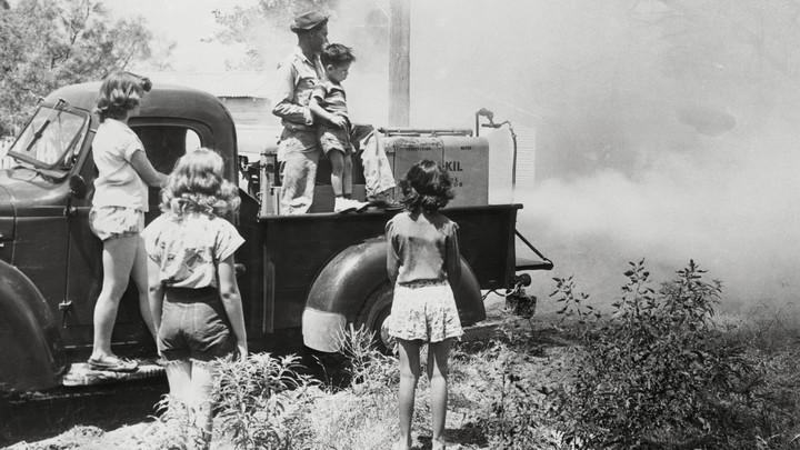 Children in San Angelo watch as DDT sprays over their community.