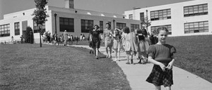 Black-and-white photo of 1940s children walking down a path leading from an Art Deco school building.
