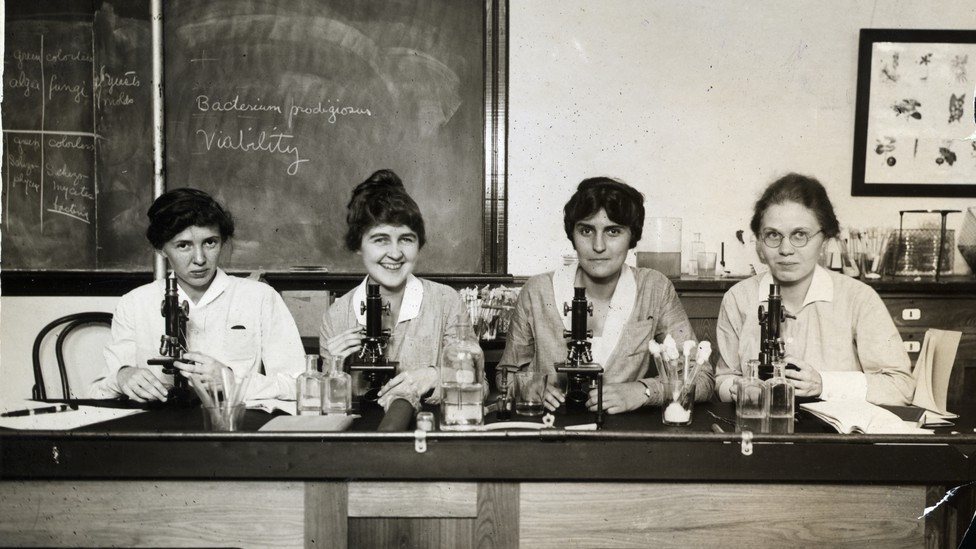 Women seated before microscopes in an undated photo