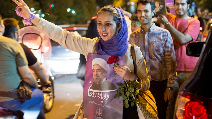 Woman holds a poster of Iranian President Hassan Rouhani during a campaign rally in Tehran.
