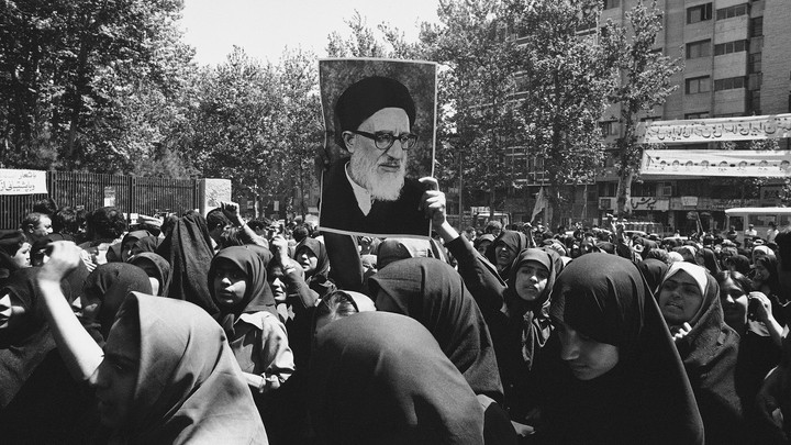 Iranian women wearing chadors hold up a painting of Ayatollah Taleghani.