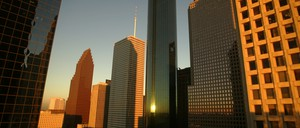 Buildings in downtown Houston reflect the light of the setting sun.