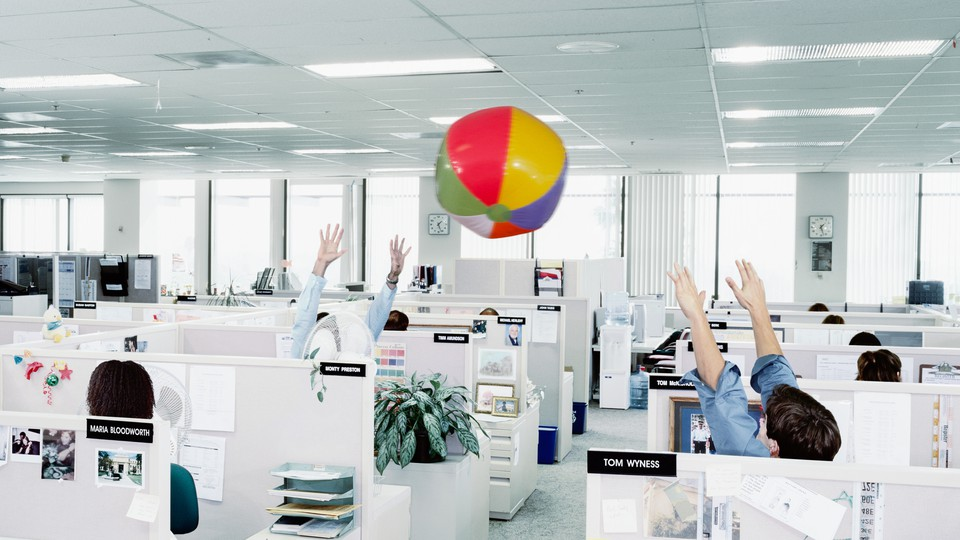 Workers throw a beachball in an office.