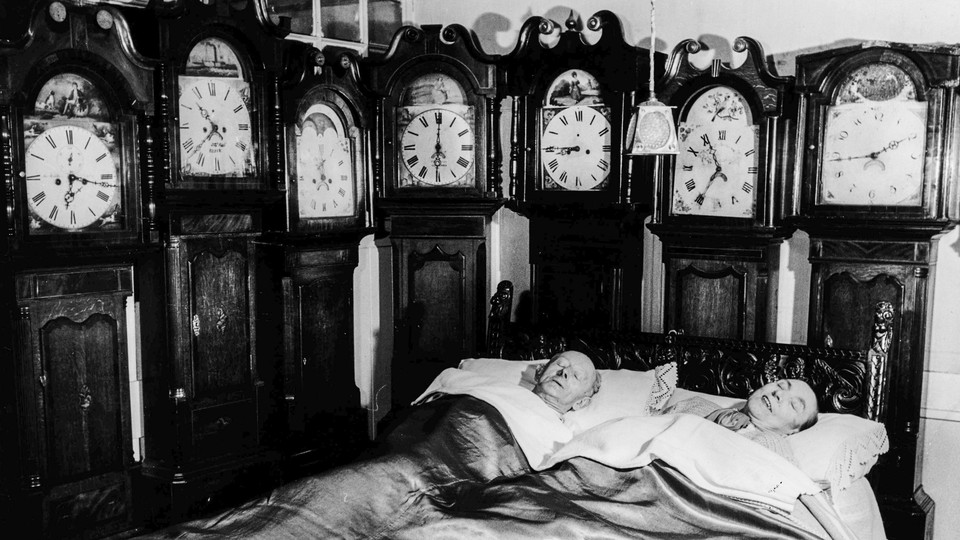 A man and woman sleep in a room full of antique clocks.