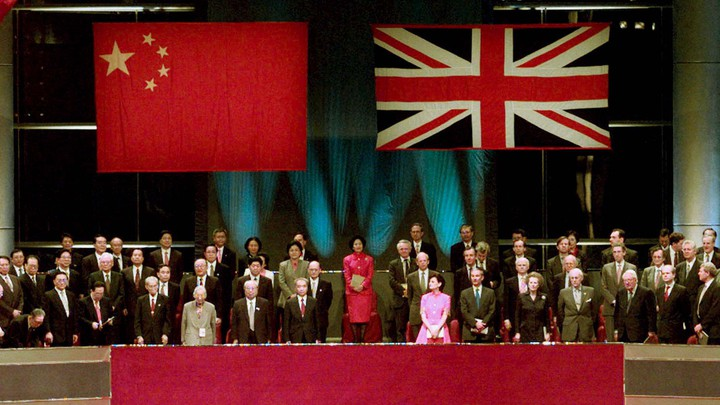 Chinese and British leaders stand beneath the flags of China and the United Kingdom.