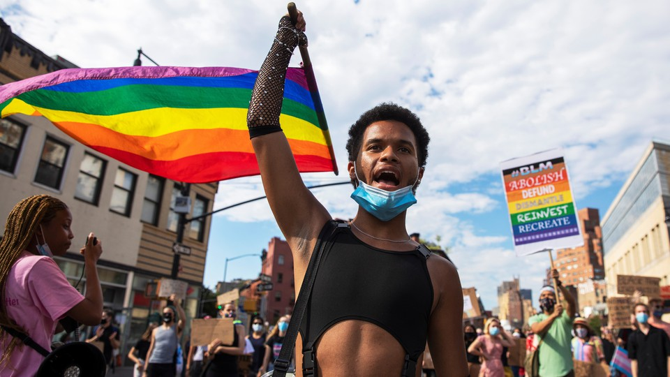 Pride marchers carrying rainbow flags and Black Lives Matter signs