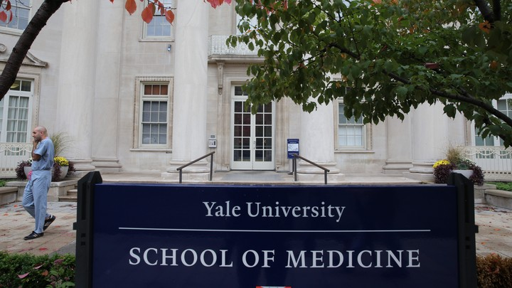 A man in scrubs walks outside the Yale School of Medicine.