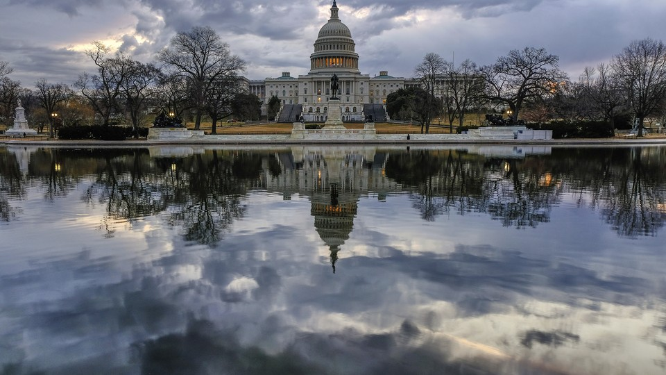 The Capitol is reflected in a pool in front of the building.
