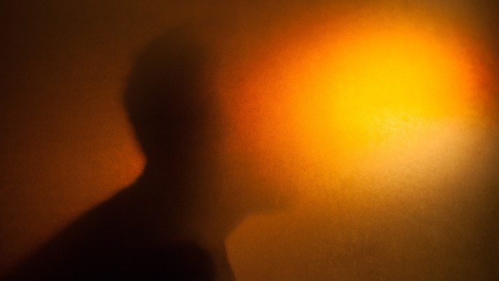 A silhouette with the face blurred out by a bright orange light