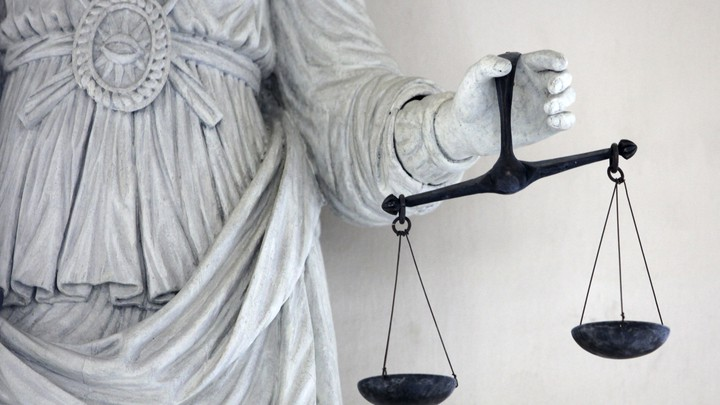The hand of a stone statue holds a black scale of justice.