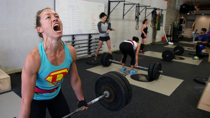 A woman makes an intense face while doing a deadlift during a CrossFit workout.