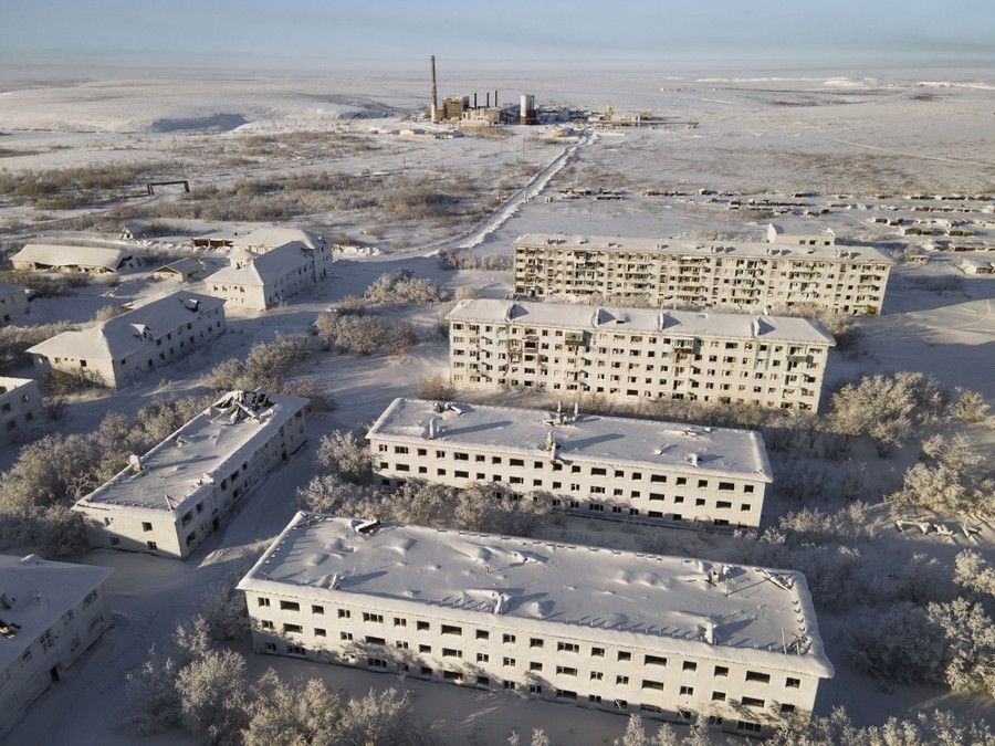 An aerial view of snow- and ice-covered abandoned buildings, with a snow-covered, largely treeless landscape in the background.