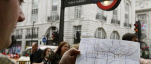 photo: a commuter looks at a small map of the London Tube in 2009