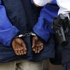 A police officer escorts a man in handcuffs