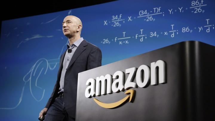 """Jeff Bezos standing next to a podium that says """"Amazon"""""""