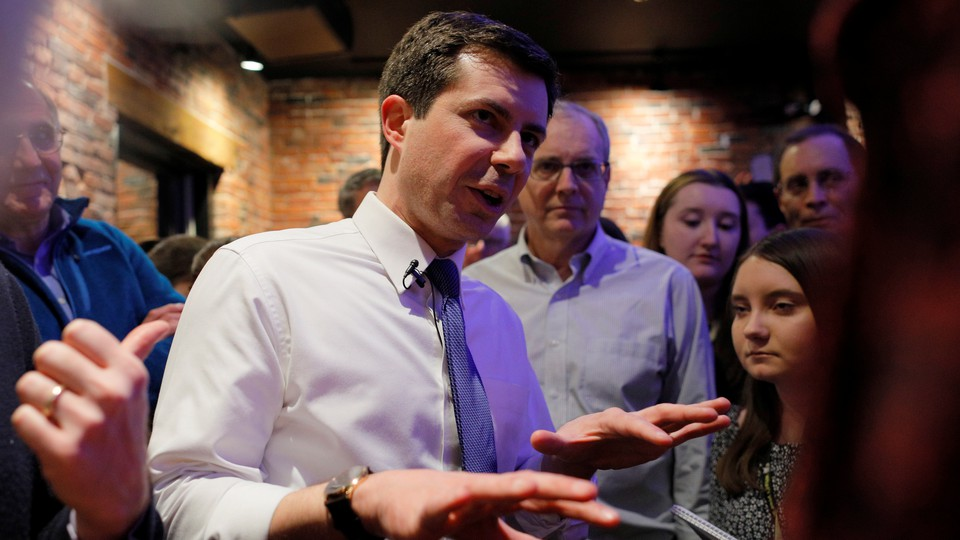 Pete Buttigieg speaks with a small cluster of people.