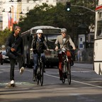 Two cyclists and a man on a skateboard travel alongside bus traffic in downtown San Francisco.