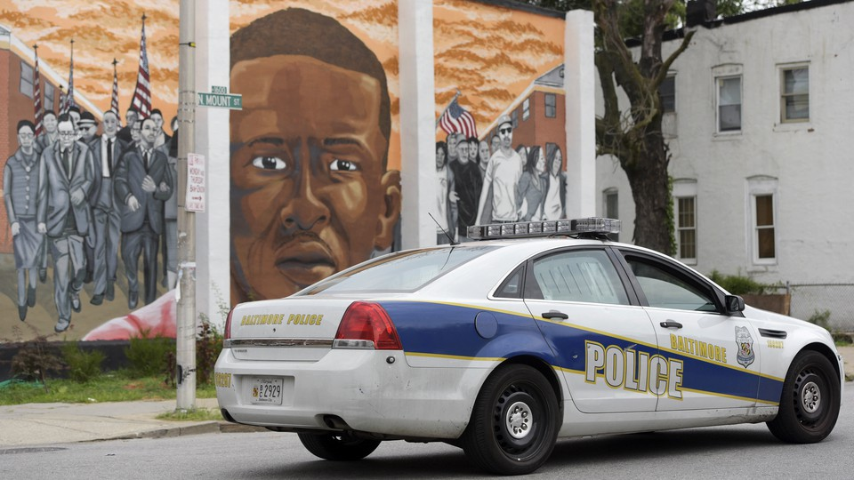 A Baltimore Police car passes a mural of Freddie Gray.