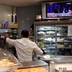 A worker serves customers at a New York diner as the result of the 2016 U.S. presidential election is shown on a TV screen.