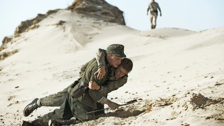 One German trooper, Anders, helps his fellow soldier, Hans, across the dunes in the Danish film, Land of Mine.