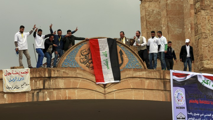 Mosul University students and activists place a national flag at the entrance of their university as they celebrate its liberation from ISIS.