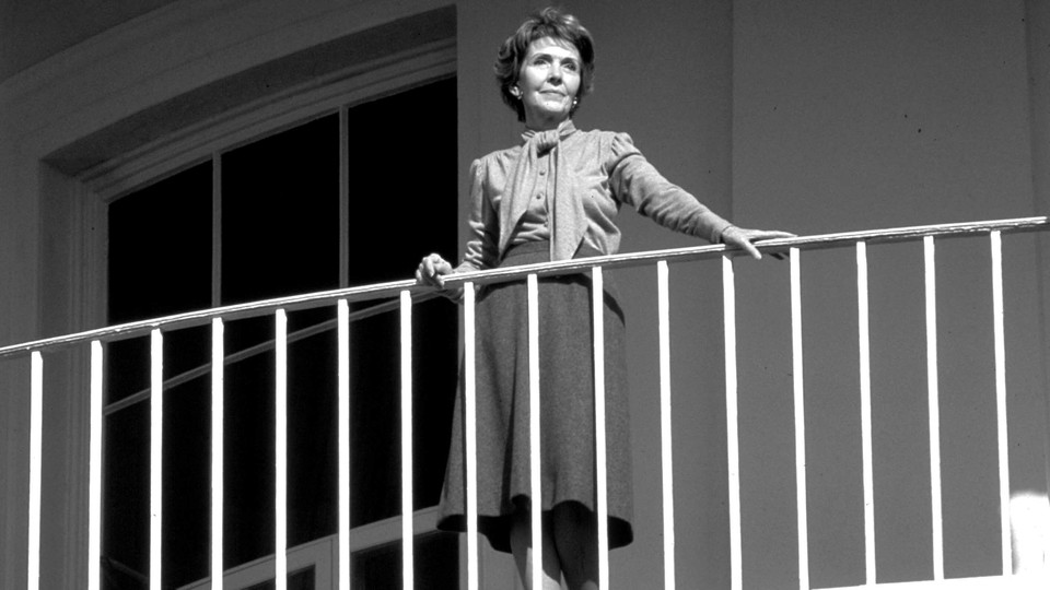 Nancy Reagan stands on a balcony, watching an unseen President Ronald Reagan depart the White House.
