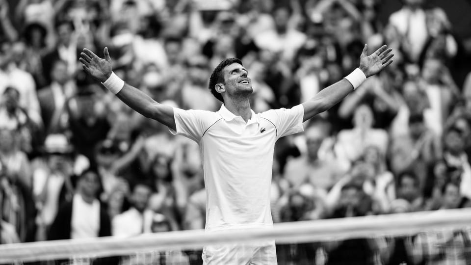A black-and-white photo of Novak Djokovic celebrating at a tennis match