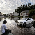 A man sits facing a flooded parking lot and apartment buildings on the other side.