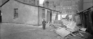 Child standing in front of early 20th century urban slum