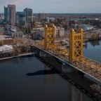 A gold-painted bridge and the skyline of Sacramento.