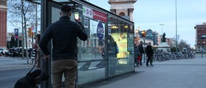Man with guide dog holds a phone aloft at a bus stop.