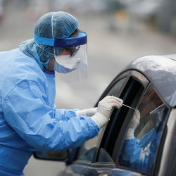 A health worker testing a patient at a drive through center in Seattle, Washington.