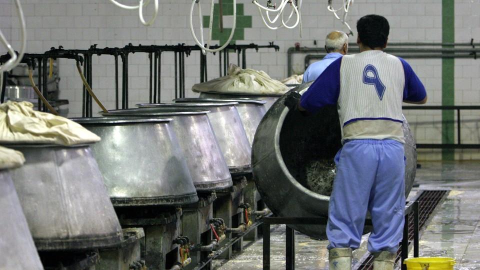 Iranian prisoners work in a kitchen in the Evin prison in Tehran, Iran, on June 13, 2006.