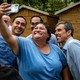 A woman wearing blue takes a selfie with three men also wearing blue