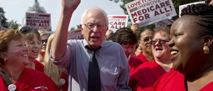 Bernie Sanders supporters hold 'Medicare for All' signs.