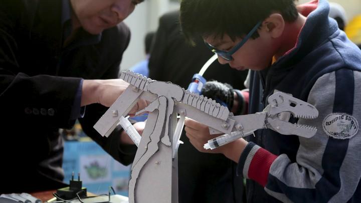 A boy builds a dinosaur robot; his teacher assists him.